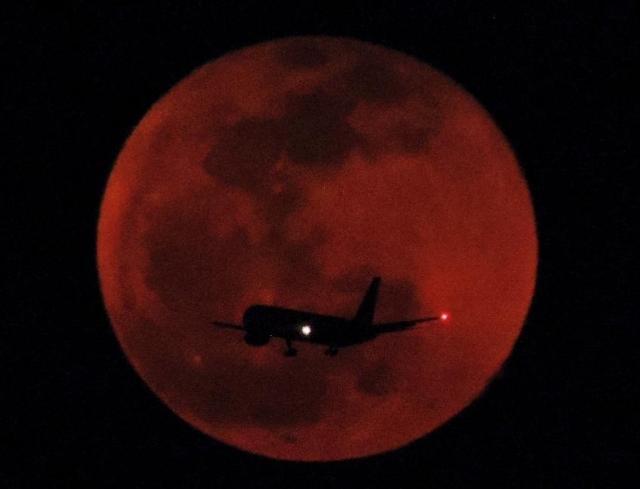 紅い満月の中を航空機が着陸態勢に